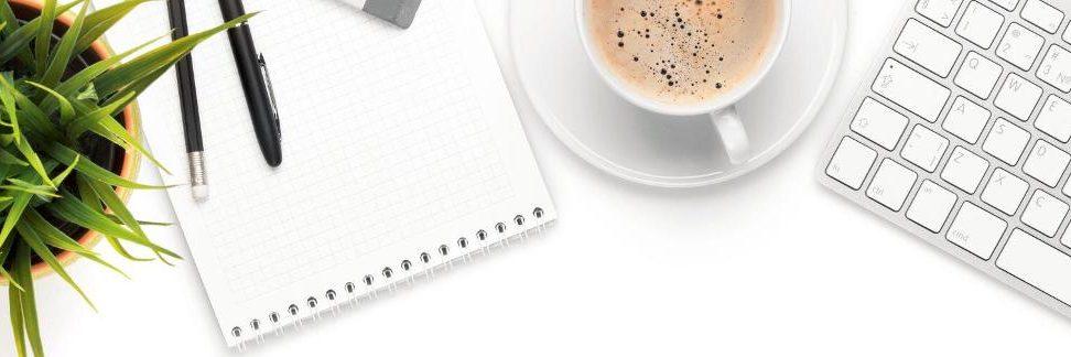 Aufgeräumter Desktop mit Kaffeetasse, Notizblock, Tastatur und grüner Pflanze